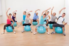 16406157 - large group of diverse people in a pilates class exercising in a gym practicing balance and control